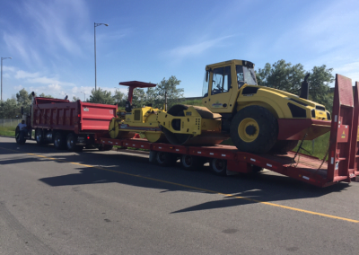 Large paving equipment loaded on to truck trailer