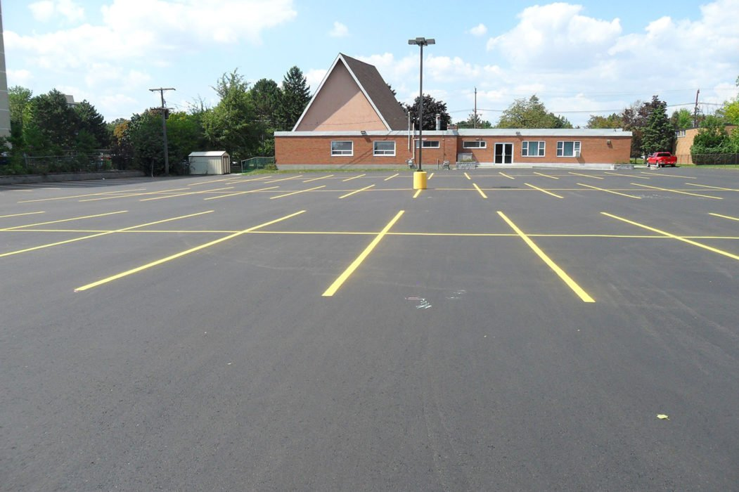 Parking lot paving project - post completion. Community centre parking lot with newly paved asphalt