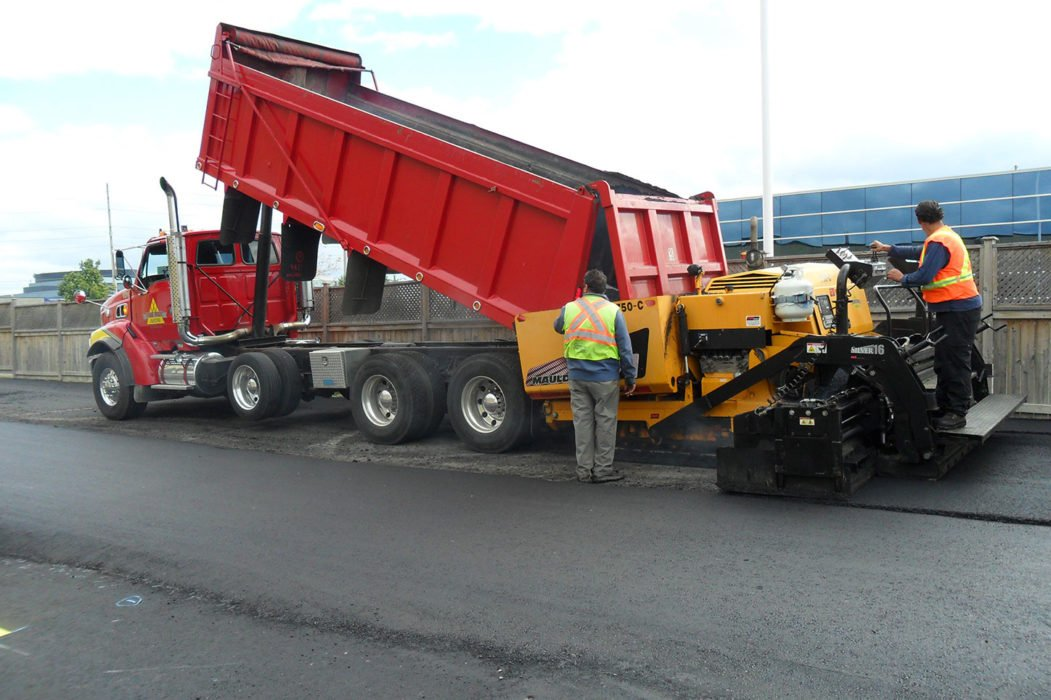 Parking lot paving project in progress - Red truck unloading asphalt as crew flattens it out using commercial asphalt equipment