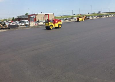 Two paving machines doing large parking lot