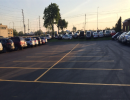 Parking lot line paint drying after new paving project - Cars parked on grass to not damage asphalt