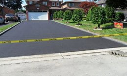 Driveway paving project after completion: Recently placed driveway asphalt in home driveway, with yellow caution tape protecting while asphalt is driveway