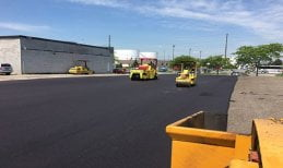 Commercial parking lot paving project in progress: Two small pavers flattening out freshly laid asphalt on industrial property